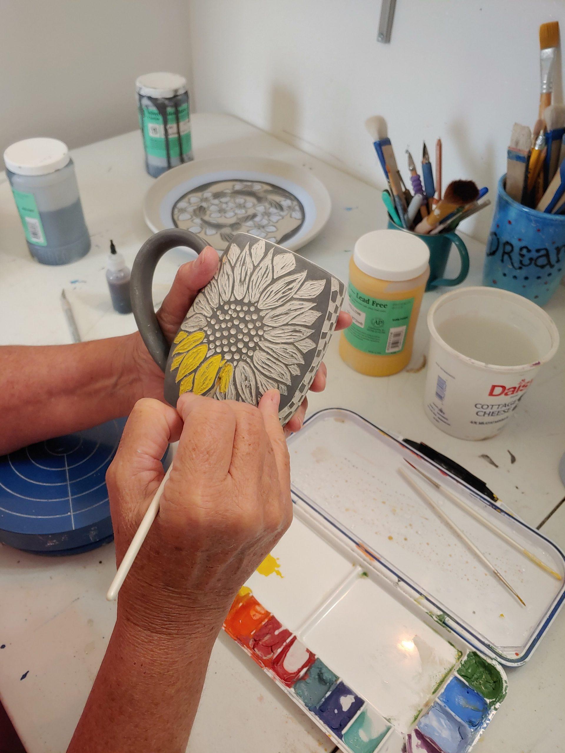Adding color to a sgrafitto carved mug with underglaze